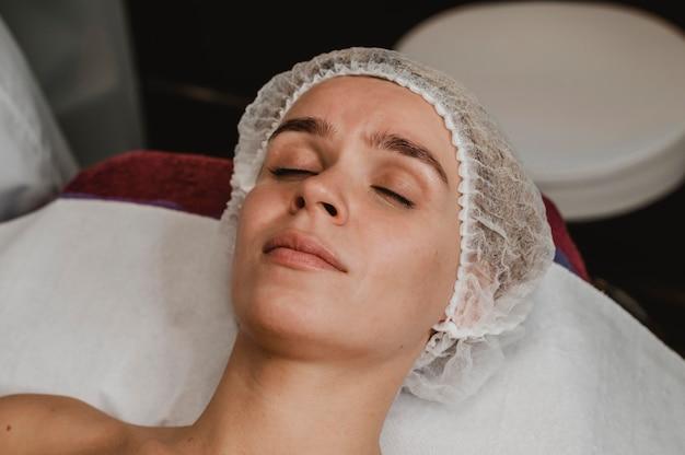 Młoda kobieta zaczyna zabieg kosmetyczny w spa