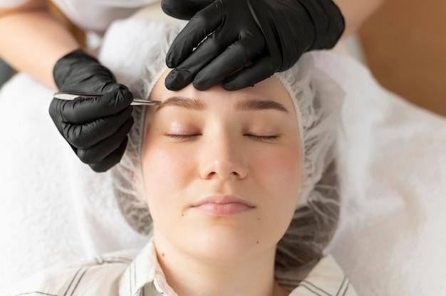 Młoda kobieta zaczyna zabieg na brwi w salonie piękności