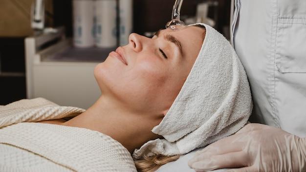 Młoda kobieta zaczyna zabieg na twarz w centrum odnowy biologicznej