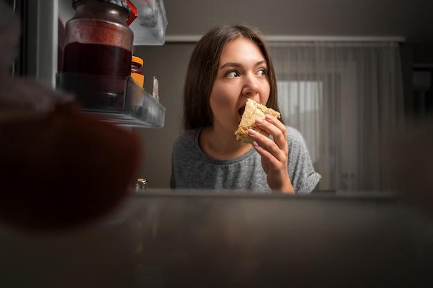 Młoda kobieta zagląda do lodówki, widok z lodówki, dziewczyna je w nocy, obawia się