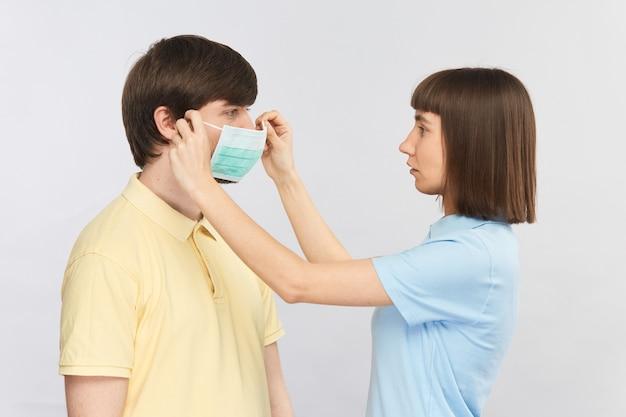Młoda kobieta zakłada maskę ochronną sterylną mężczyznę, jak założyć maskę ochronną