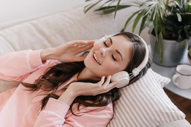 Młoda kobieta zakłada masywne słuchawki i odpoczywa na kanapie w przytulnym mieszkaniu