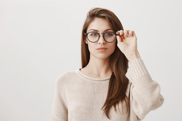Młoda kobieta zakłada okulary, wygląda na zdeterminowaną