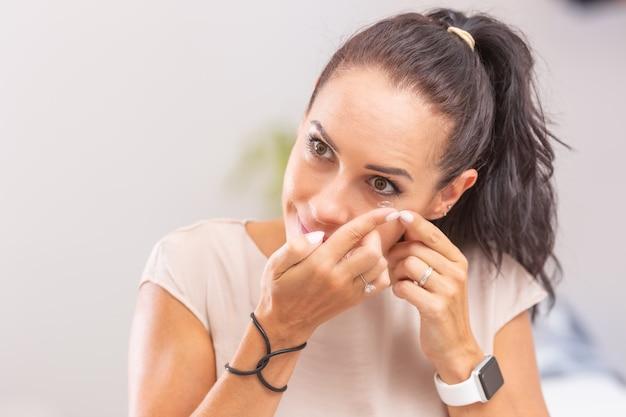 Młoda kobieta zakłada sobie soczewki kontaktowe.