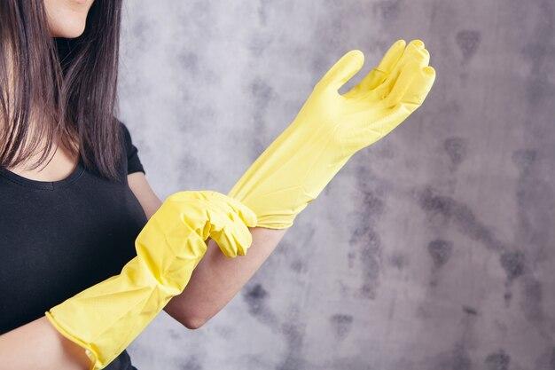 Młoda kobieta zakłada żółte gumowe rękawiczki na szarym tle