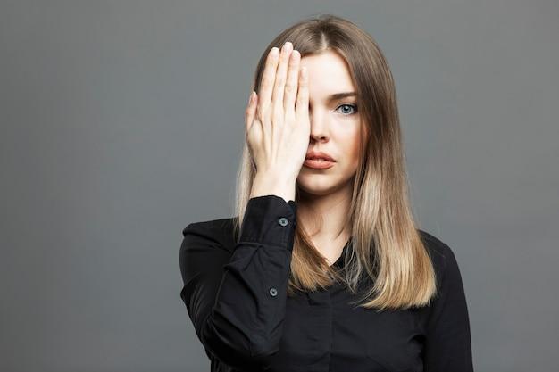 Młoda kobieta zakryła dłonią jedno oko. piękna blondynka w czarnej koszuli. teoria spiskowa i symbolika masońska. szare tło.