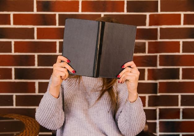 Młoda kobieta zakryła twarz książką w twardej oprawie. okładka jest czarna. zdjęcie bez twarzy.