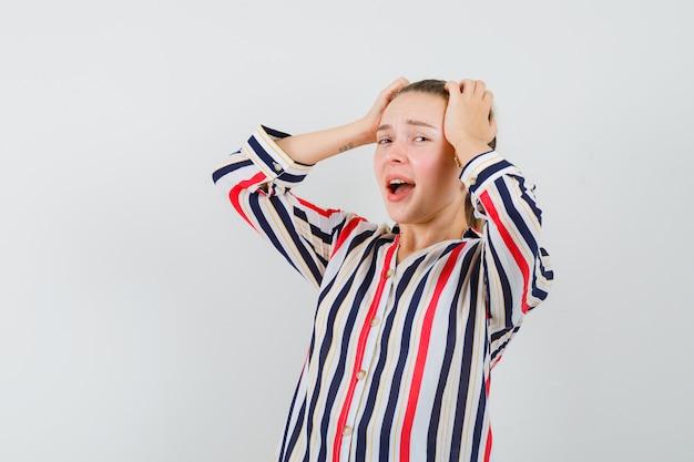 Młoda kobieta zakrywa głowę obiema rękami w bluzkę w paski i wygląda na wyczerpaną
