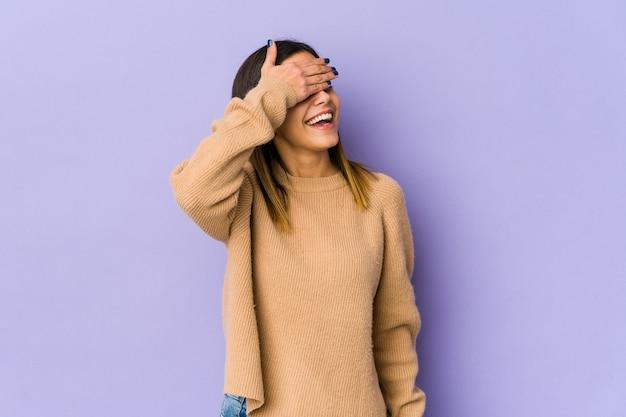 Młoda kobieta zakrywa oczy dłońmi, uśmiecha się szeroko, czekając na niespodziankę.