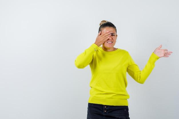 Młoda kobieta zakrywa oko dłonią, wyciąga rękę w prawo w żółtym swetrze i czarnych spodniach i wygląda na szczęśliwą