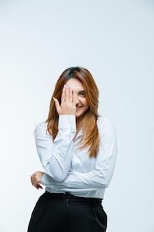 Młoda kobieta zakrywa oko ręką i wygląda na szczęśliwą