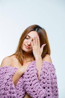 Młoda kobieta zakrywa oko ręką