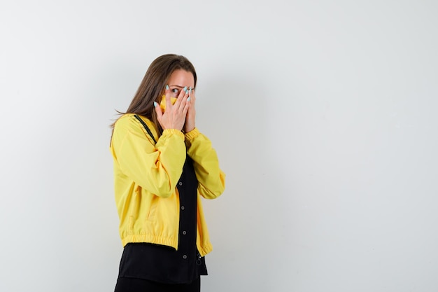 Młoda kobieta zakrywa twarz dłonią i wygląda na przestraszoną
