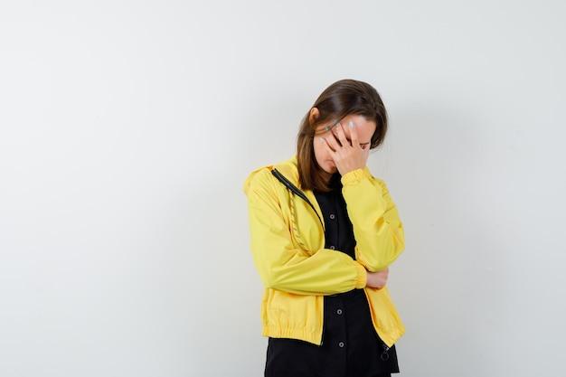 Młoda kobieta zakrywa twarz ręką i wygląda na zestresowaną