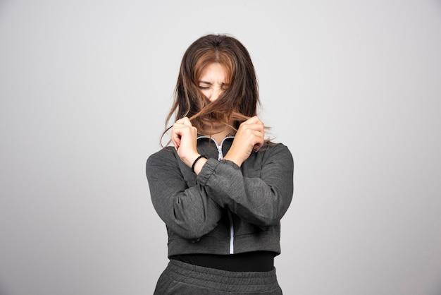 Młoda kobieta zakrywa twarz z włosami.