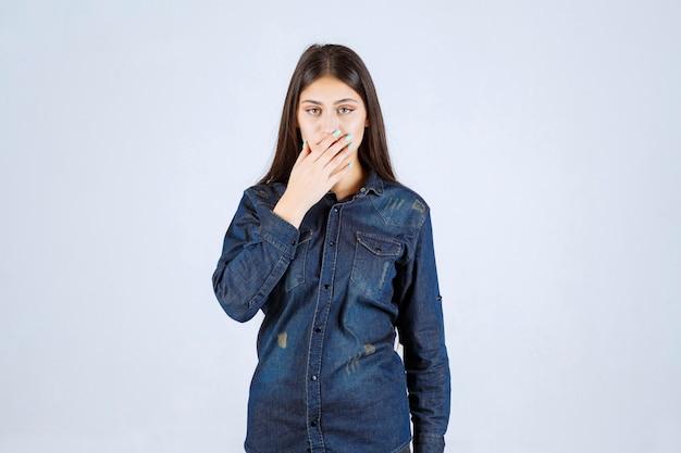 Młoda kobieta zakrywa usta i milczy