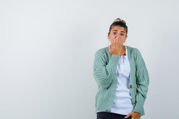Młoda kobieta zakrywa usta ręką w białej koszulce i miętowozielonym swetrze i wygląda na zaskoczoną
