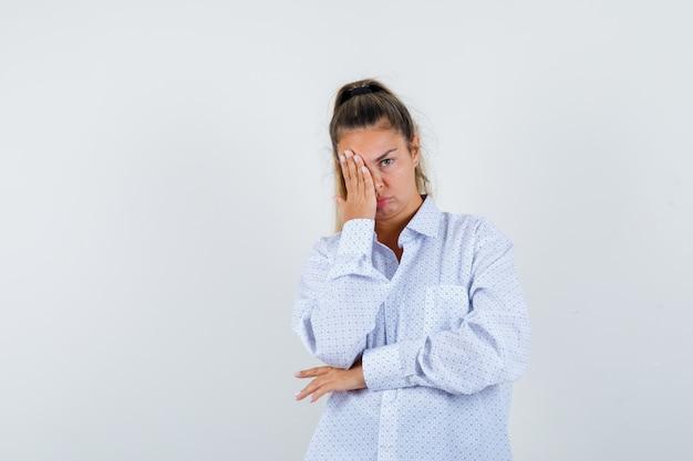 Młoda kobieta zakrywająca część twarzy ręką w białej koszuli i wyglądająca na zmęczoną