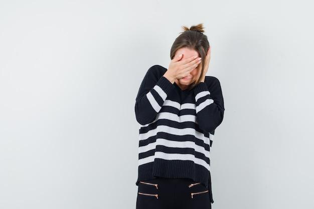 Młoda kobieta zakrywająca oczy dłonią, kładąc drugą dłoń na uchu w dzianinie w paski i czarnych spodniach i wyglądająca na udręczoną