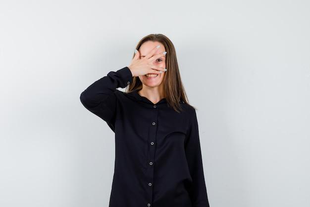 Młoda kobieta zakrywająca oczy dłonią
