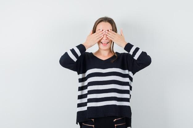 Młoda kobieta zakrywająca oczy obiema rękami w dzianinie w paski i czarne spodnie i wyglądająca na szczęśliwą