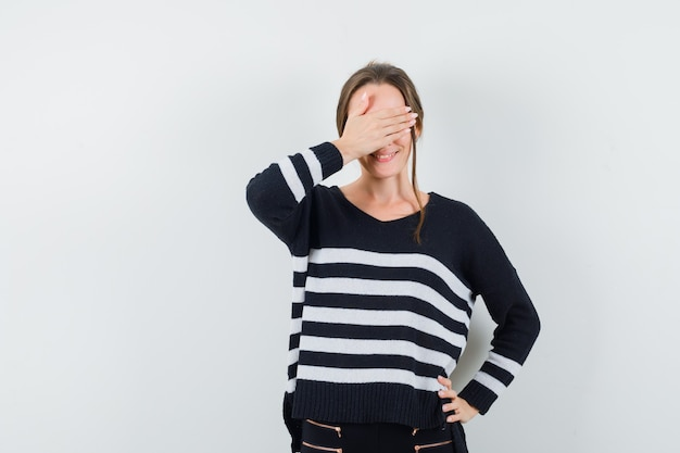 Młoda kobieta zakrywająca oczy rękami trzymając się za ręce w pasie w dzianinie w paski i czarne spodnie i wyglądająca na szczęśliwą