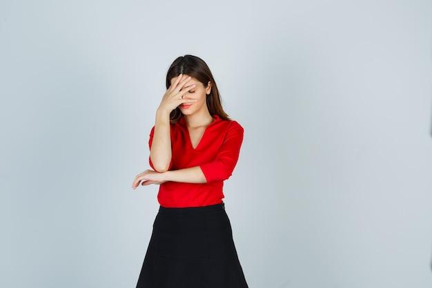 Młoda kobieta zakrywająca twarz ręką w czerwonej bluzce, czarnej spódnicy i wyglądająca na zirytowaną