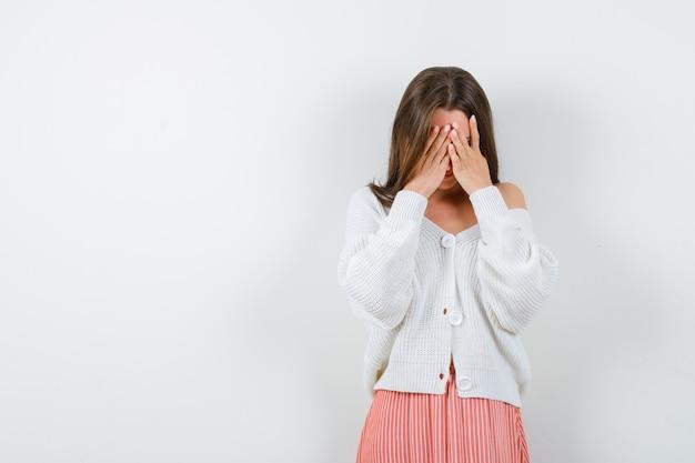 Młoda kobieta zakrywająca twarz rękami w sweter i spódnicę patrząc przygnębiony na białym tle