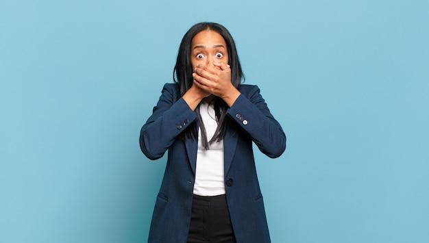 """Młoda kobieta zakrywająca usta dłońmi ze zszokowanym, zdziwionym wyrazem twarzy, zachowująca tajemnicę lub mówiąca """"ups"""""""