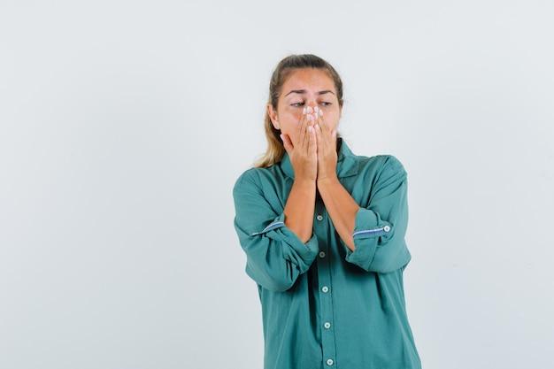 Młoda kobieta zakrywająca usta i nos rękami w zielonej bluzce i wyglądająca na zirytowaną