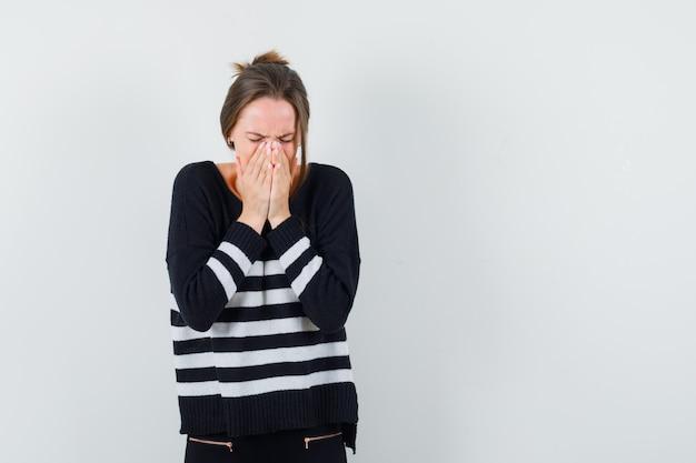 Młoda kobieta zakrywająca usta rękami w pasiastej dzianinie i czarnych spodniach i wyglądająca ponuro