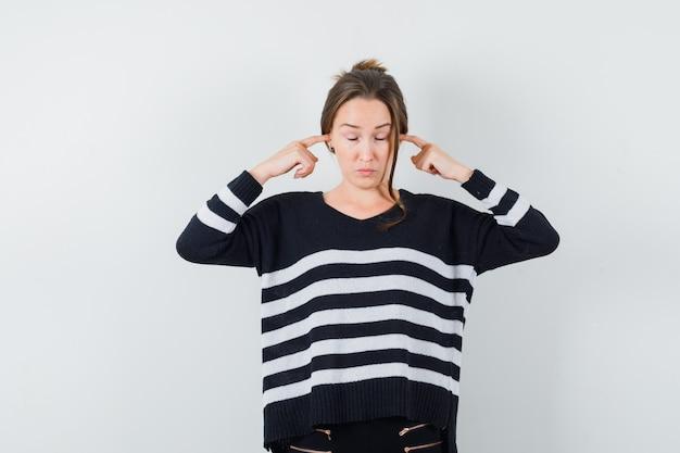 Młoda kobieta zakrywająca uszy palcami wskazującymi w dzianinie w paski i czarne spodnie i wyglądająca na skupioną