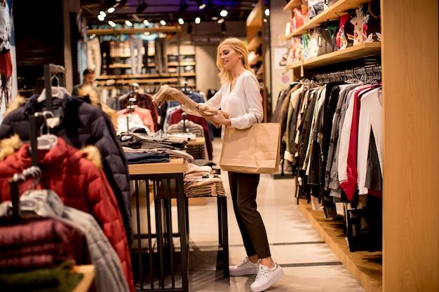 Młoda kobieta zakupy i wyszukiwanie wśród ubrań w sklepie z ubraniami