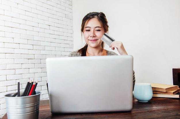 Młoda kobieta zakupy lub dokonywanie płatności kartą kredytową w domu