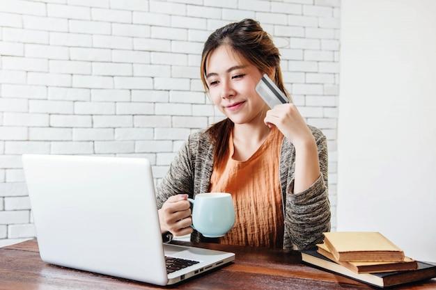 Młoda kobieta zakupy lub dokonywanie płatności kartą kredytową