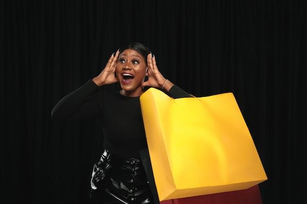 Młoda kobieta zakupy z kolorowych opakowań na czarnej ścianie