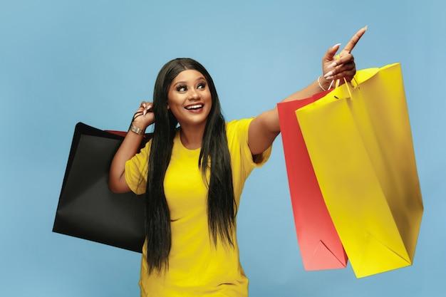Młoda kobieta zakupy z kolorowymi paczkami na niebieskiej ścianie
