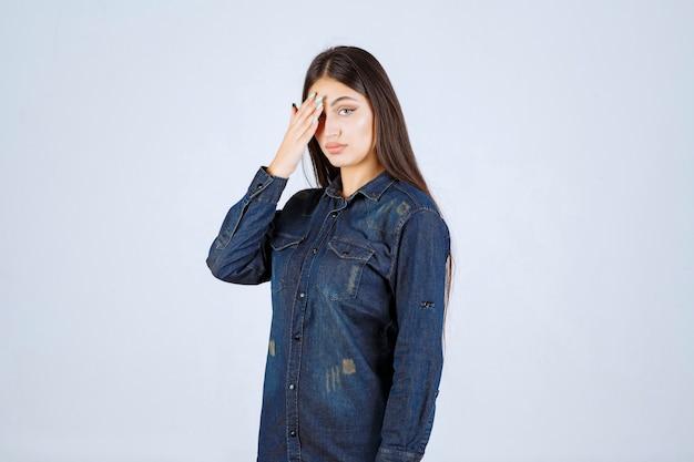 Młoda kobieta zamyka oczy lub część twarzy i patrzy przez palce
