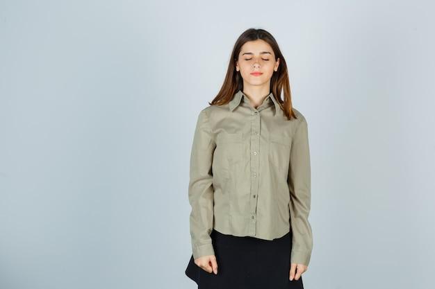 Młoda kobieta zamykając oczy w koszuli, spódnicy i marzycielskim wyglądzie
