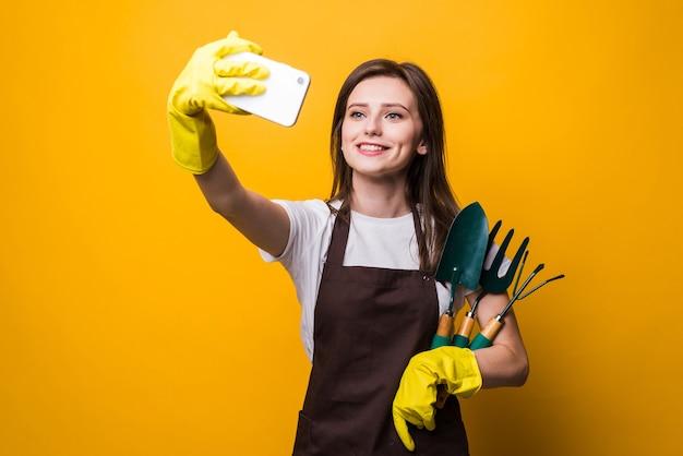 Młoda kobieta zapałka bierze selfie na telefon, trzymając narzędzia na białym tle