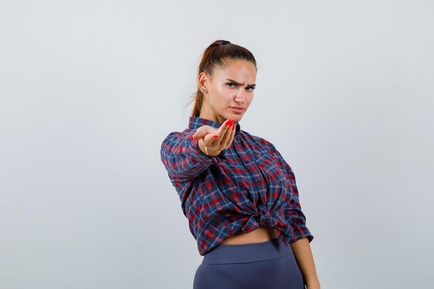 Młoda kobieta zaprasza w kraciastą koszulę, spodnie i wygląda poważnie, widok z przodu.