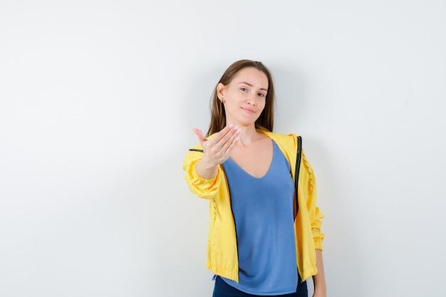 Młoda kobieta zapraszająca w koszulce, kurtce i wyglądająca pewnie. przedni widok.