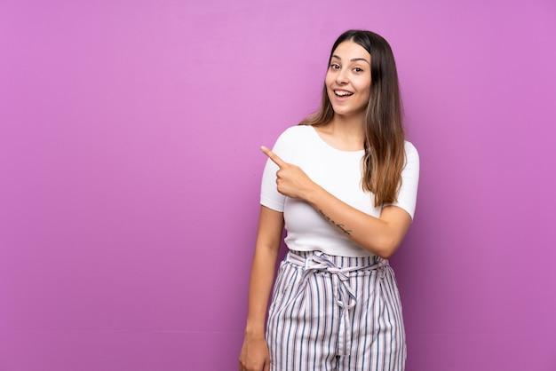 Młoda kobieta zaskakująca i wskazuje strona