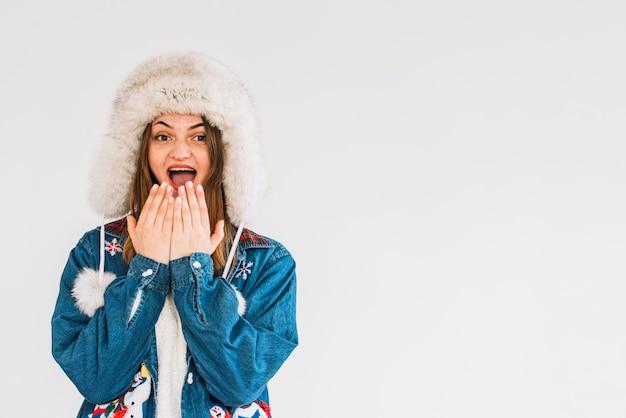 Młoda kobieta zaskoczony w futro kapelusz z rąk w pobliżu podbródka
