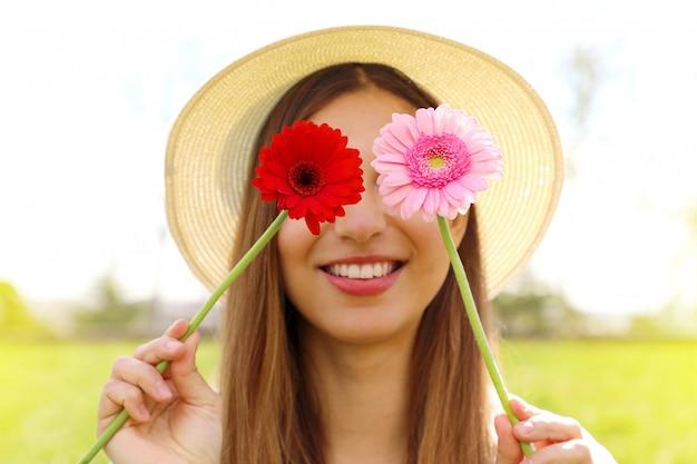 Młoda kobieta zasłaniając oczy kolorowymi kwiatami