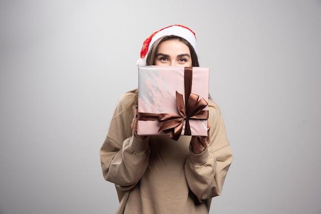 Młoda kobieta zasłaniająca twarz prezentem bożonarodzeniowym.