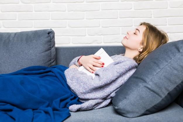 Młoda kobieta zasnęła podczas czytania, leżąc na plecach w łóżku z książką opartą na brzuchu