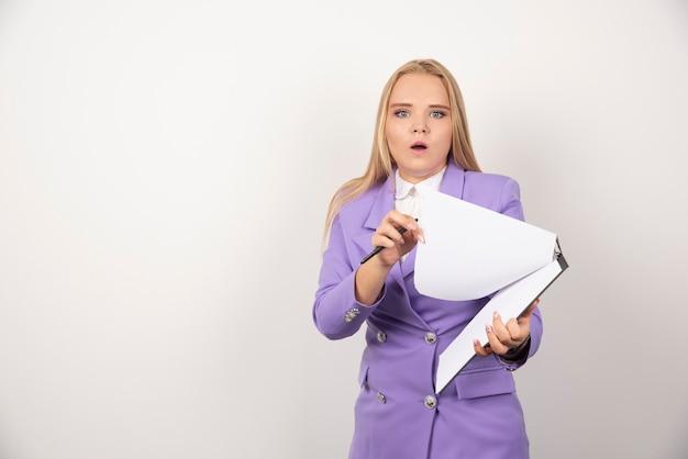 Młoda kobieta zastanawia się z ołówkiem i tabletem na białym.