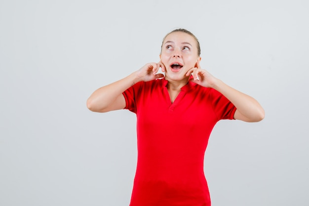 Młoda kobieta zatyka uszy palcami w czerwonej koszulce i patrząc podekscytowany