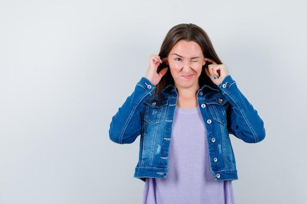 Młoda kobieta zatykając uszy palcami w t-shirt, kurtkę i znudzony. przedni widok.